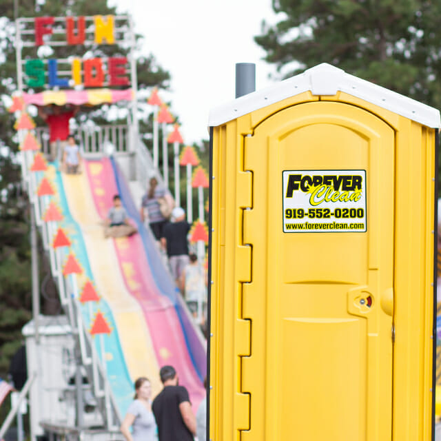 forever clean portable restroom in front of fair slide
